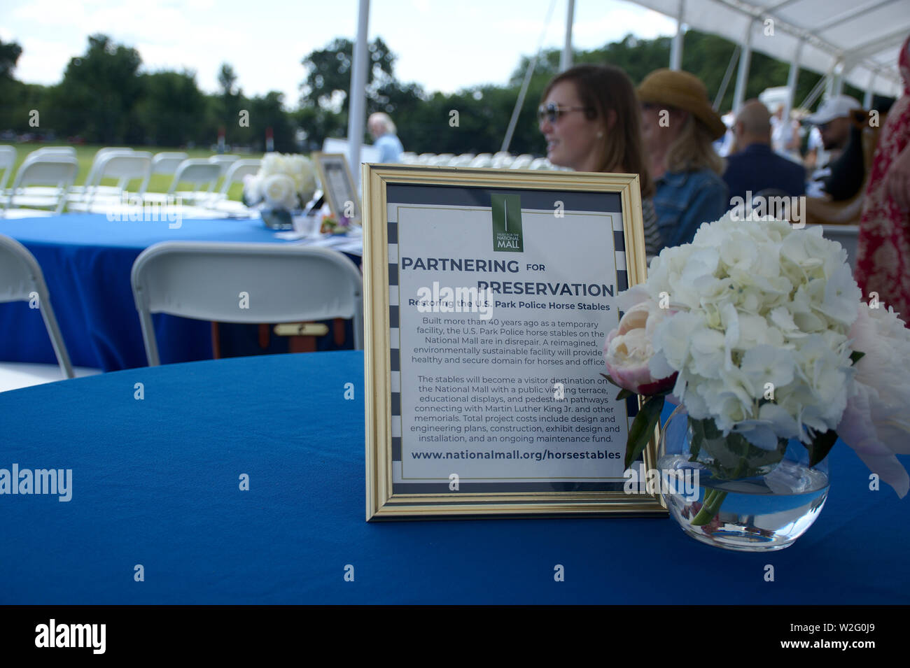 District Cup Polo match covered tent area with purpose of event sign and flower in clear vase on a table - Stock Image