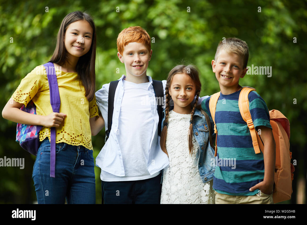 Group of happy interracial friends with satchels standing in park and embracing each other while posing for camera Stock Photo