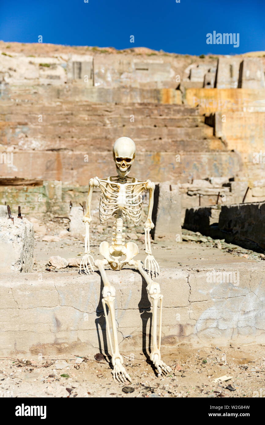 Skeleton posing in mining ruins in the desert on a hot day