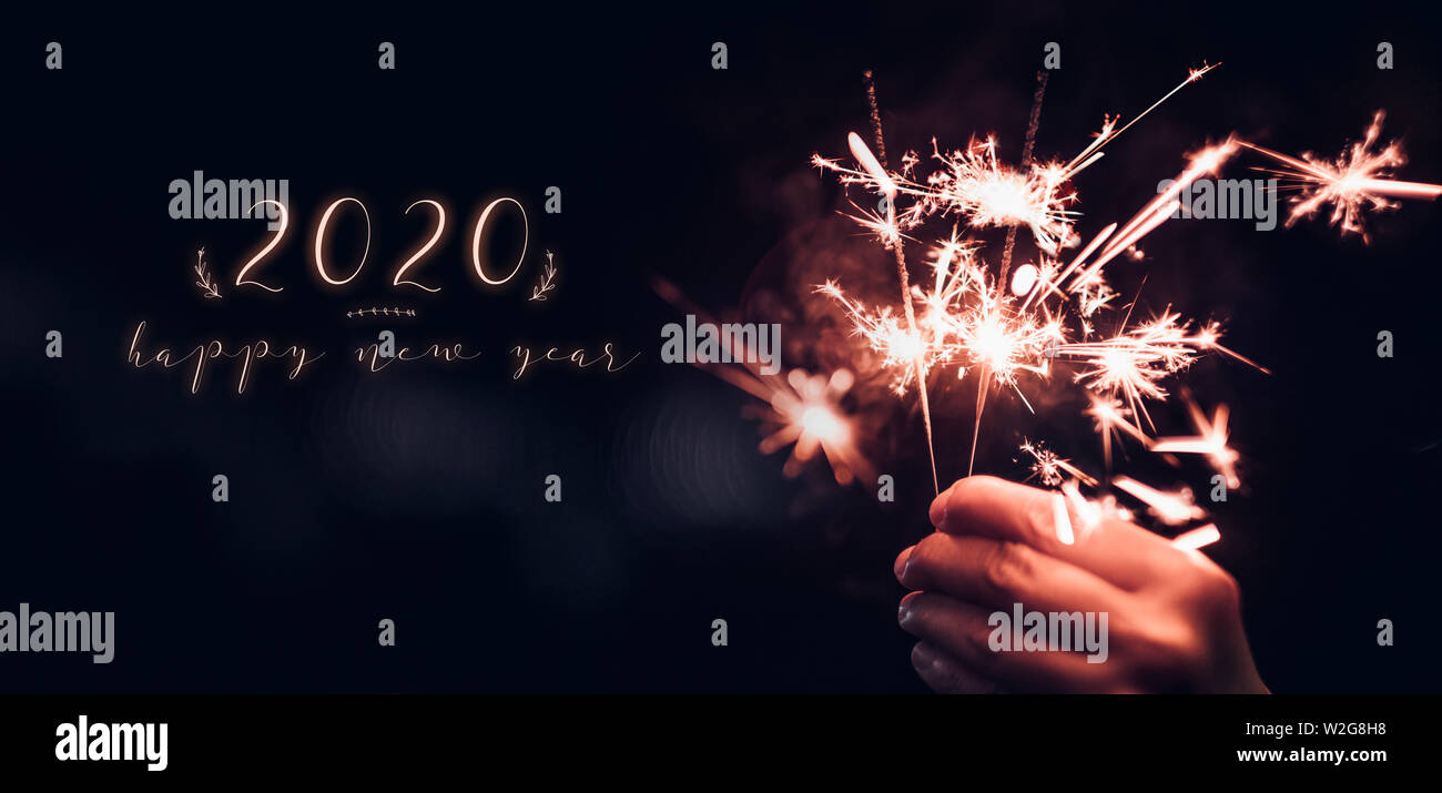 happy new year 2020 high resolution stock photography and images alamy https www alamy com happy new year 2020 text with hand holding burning sparkler firework blast with on a black bokeh background at nightholiday celebration event partyd image259742820 html