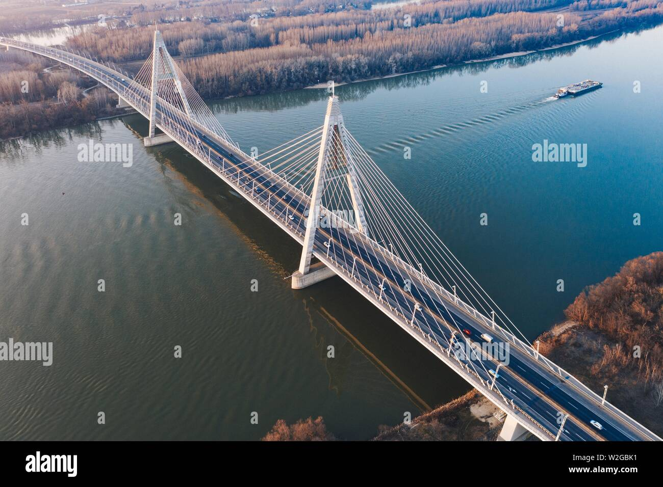 An aerial beautiful shot of a suspension bridge over a large river with a boat sailing in it - Stock Image