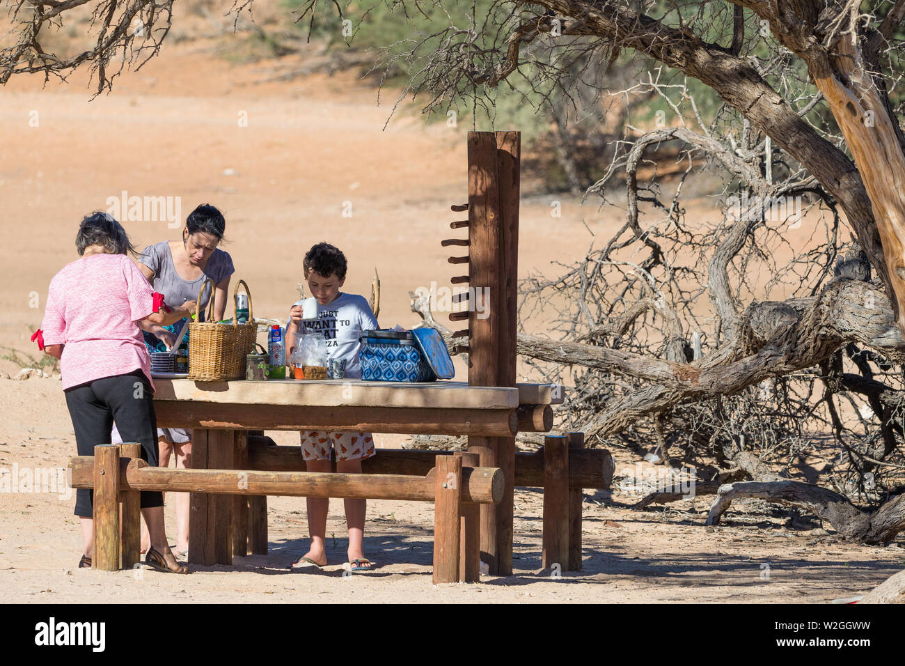 Remarkable Family Group At A Wooden Bench Table Preparing A Meal At A Beatyapartments Chair Design Images Beatyapartmentscom