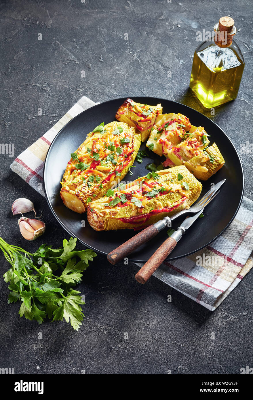 Stuffed zucchini with tomato slices, onion and cheese served on a black plate with fork and knife, vertical view from above - Stock Image