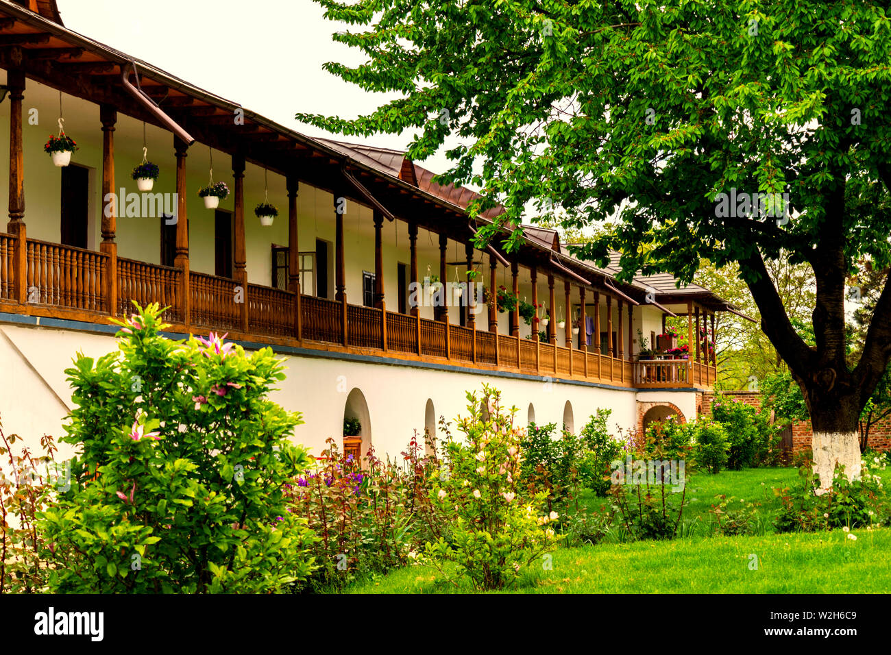 old style rustic house with laborious wood porch and front green garden tree Stock Photo