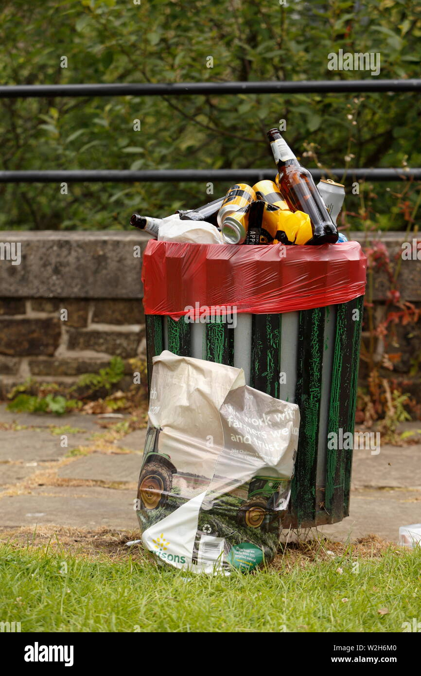 Beer bottle and aluminium drinks cans thrown away in overfilled street litter bin, plastic bag with litter on ground next to footpath. ramsbottom uk Stock Photo
