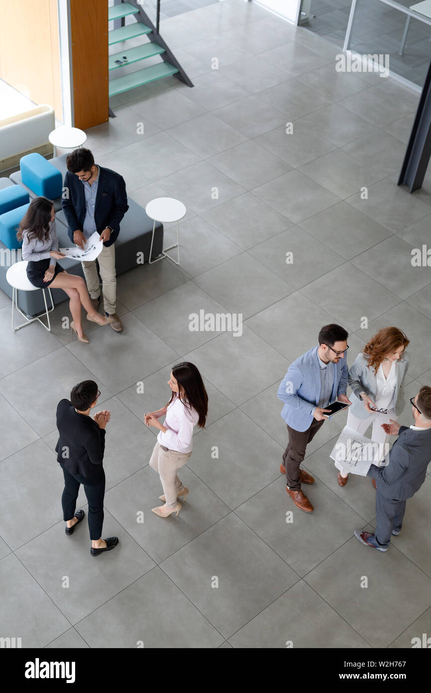 Business people working together in office hall. - Stock Image