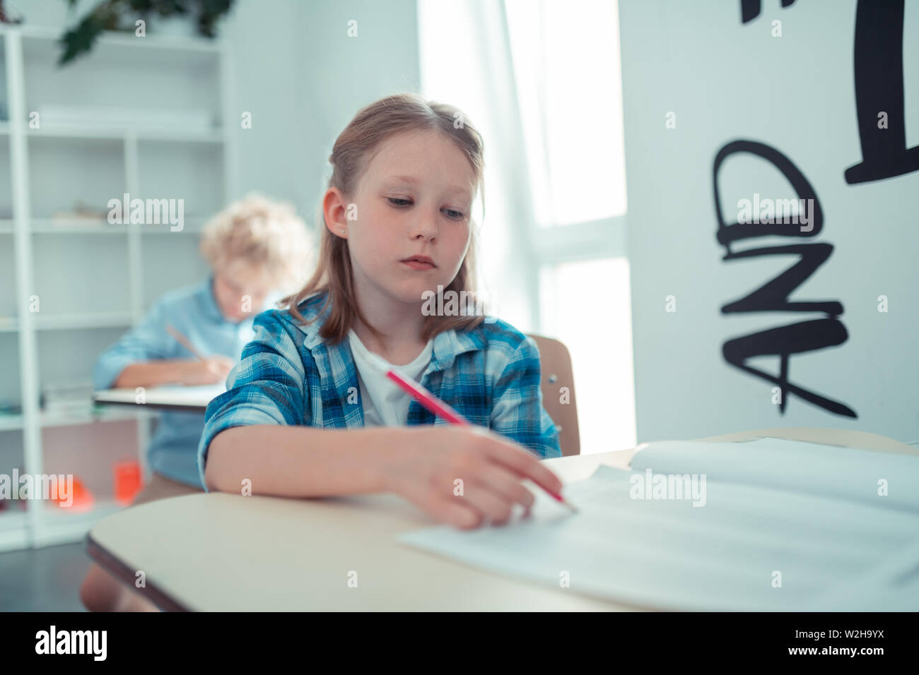 Tired school girl writing her maths test. Stock Photo