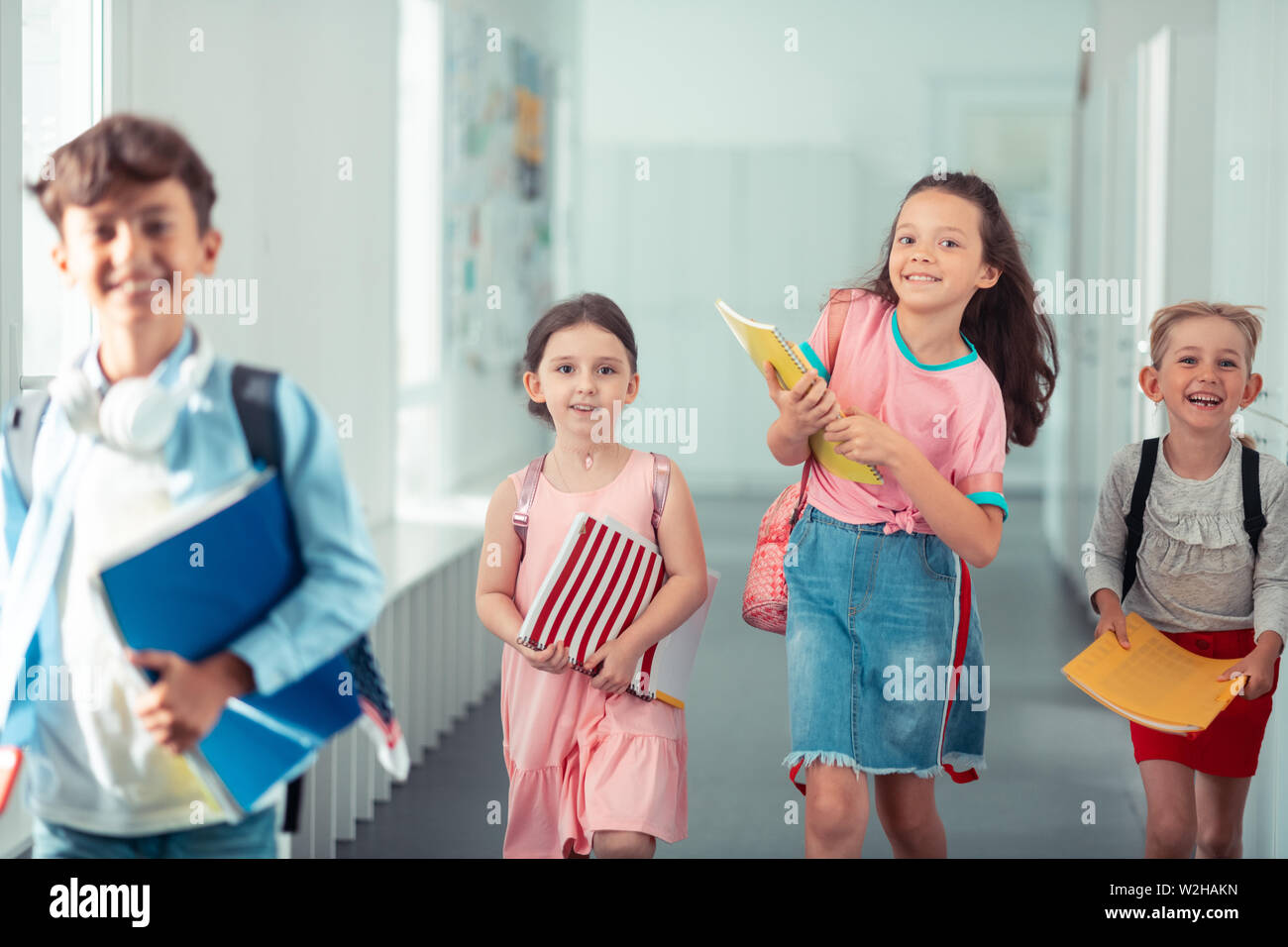 Girls and boy feeling happy going home from school - Stock Image