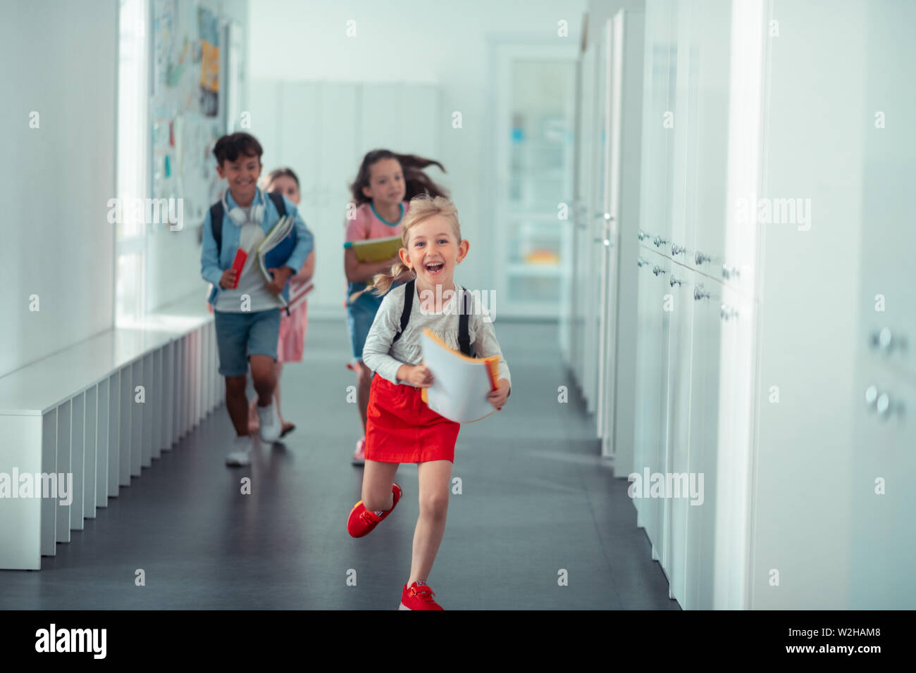 Happy girl wearing red skirt running home from school - Stock Image