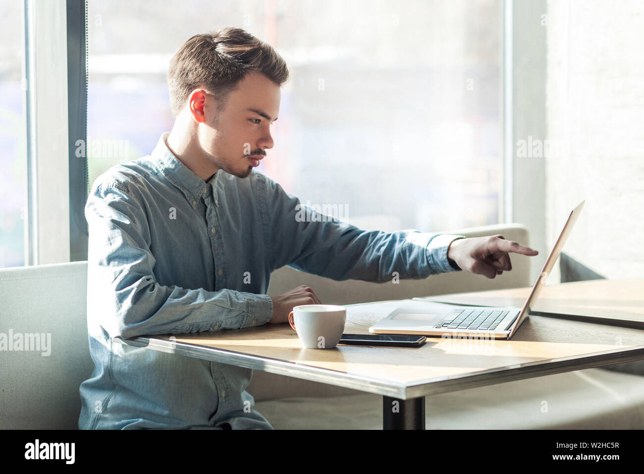Side view portrait of serious young businessman in blue shirt are sitting and pointing at target on laptop dislpay with attention and serious face. in Stock Photo