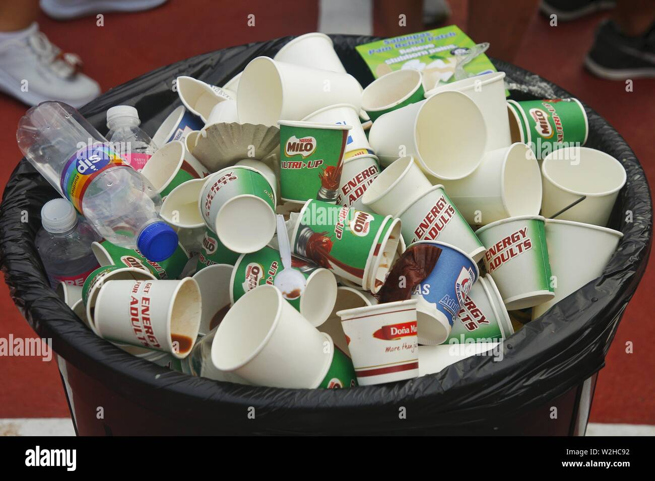 QUEZON CITY, PHILIPPINES – JULY 7, 2019: Plastic and paper cups in a garbage or trash bin and feet of people standing next to it. - Stock Image