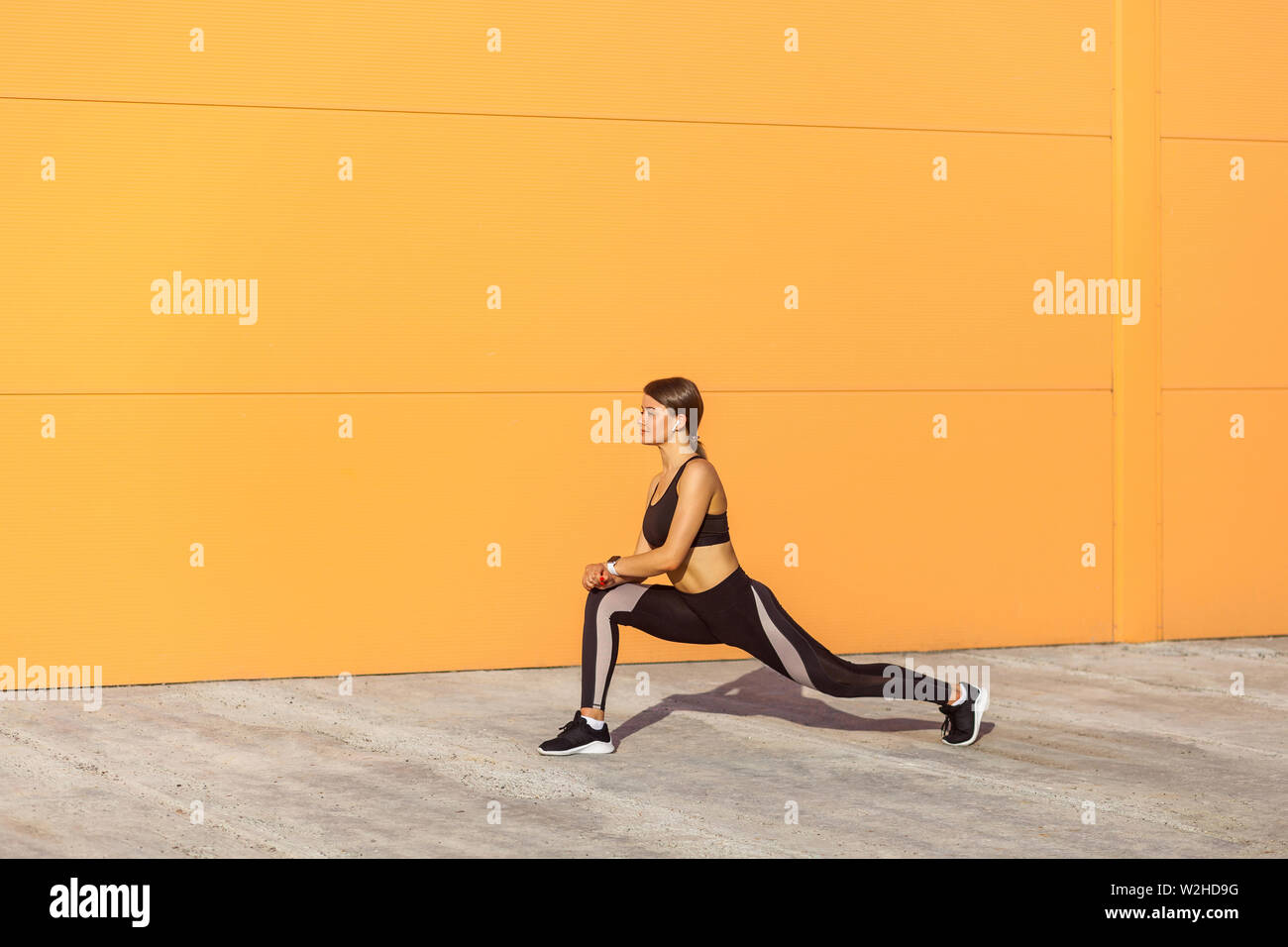 Young attractive sporty woman wearing black sporwear practicing sport exercises in morning on street, stretching legs and standing on ashtanga pose, o Stock Photo