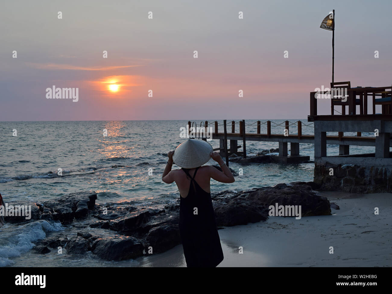 Young attractive woman at the seashore in Vietnam wearing a typical hat staring at the sunset. Young lady watching sunset over the South China Sea in the pier. Stock Photo