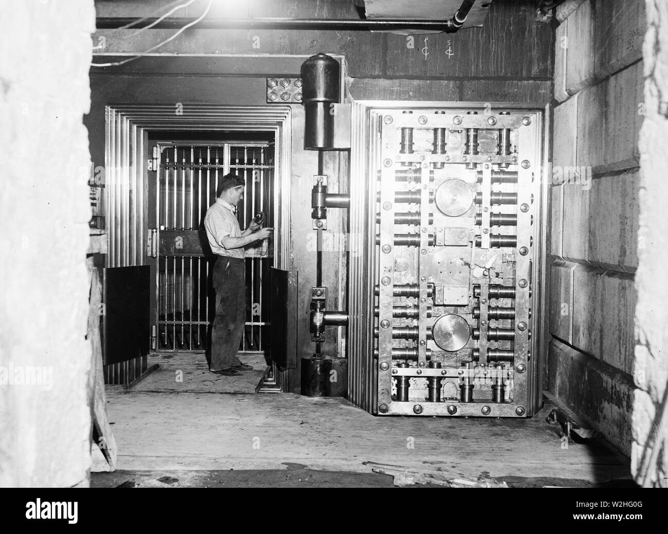 Man working on a large bank vault area ca. 1934 - Stock Image