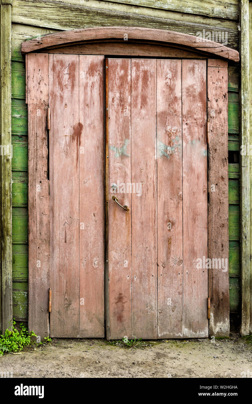 Old wooden door with the wooden carved architrave - Stock Image