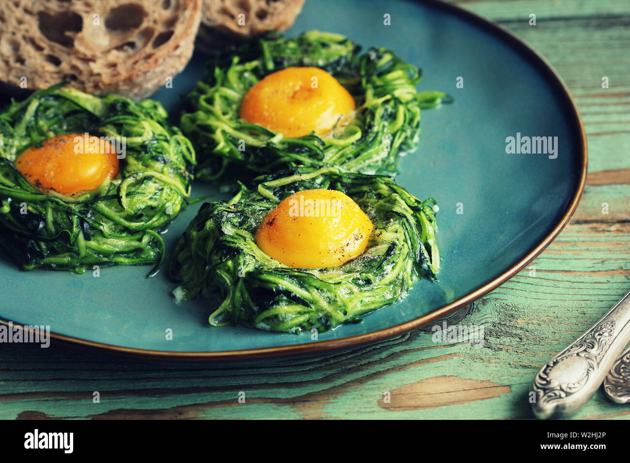 Fried egg in zucchini noodle nest, healthy breakfast, top view - Stock Image