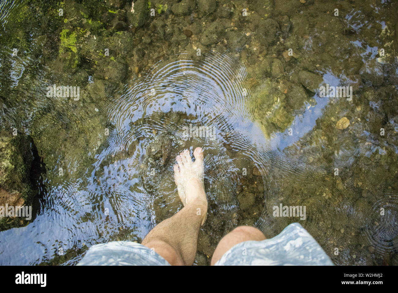 Left Male Barefoot In Shallow River - Stock Image