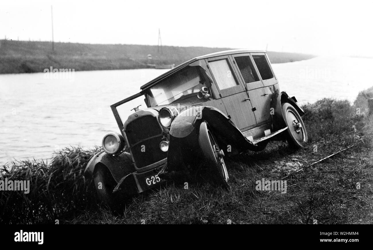 Traffic accident with passenger car on the roadside next to a canal ca. 1930 Stock Photo