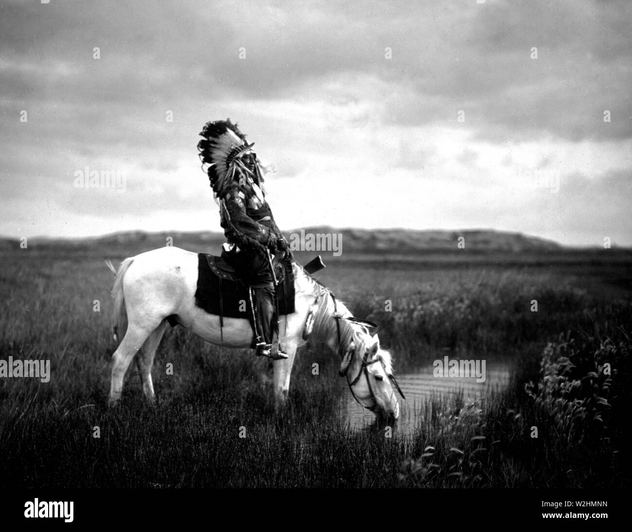 Edward S Curtis Native American Indians Red Hawk An Oglala Warrior Sitting On A Horse That Is Drinking From A Small Pond In The Badlands Ca 1905 Stock Photo Alamy