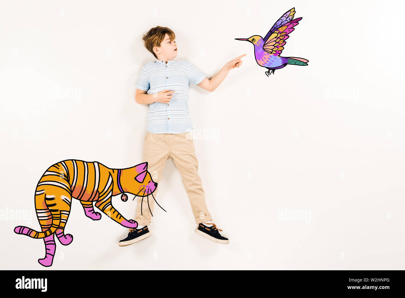 top view of surprised kid pointing with finger humming bird near orange cat on white - Stock Image