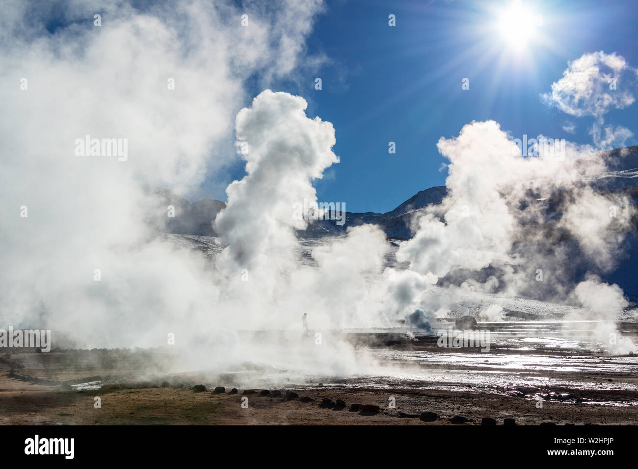 El Tatio geysers in Chile, Silhouette of a man walking among the steams and fumaroles at sunrise - Stock Image