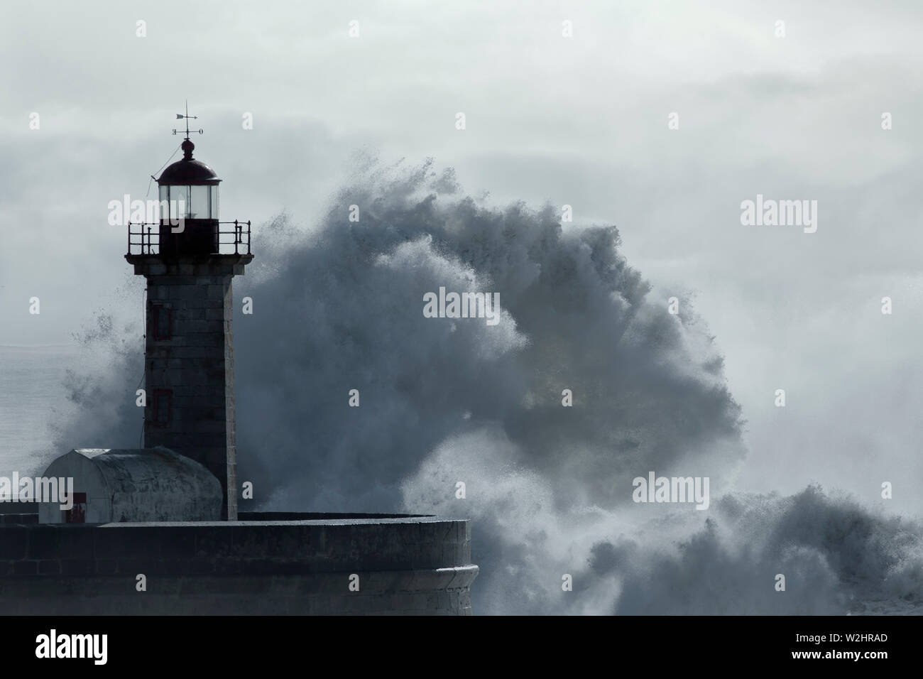 Soft backlit big wave splash. Old pier and lighthouse of Douro river mouth. Toned blue. - Stock Image