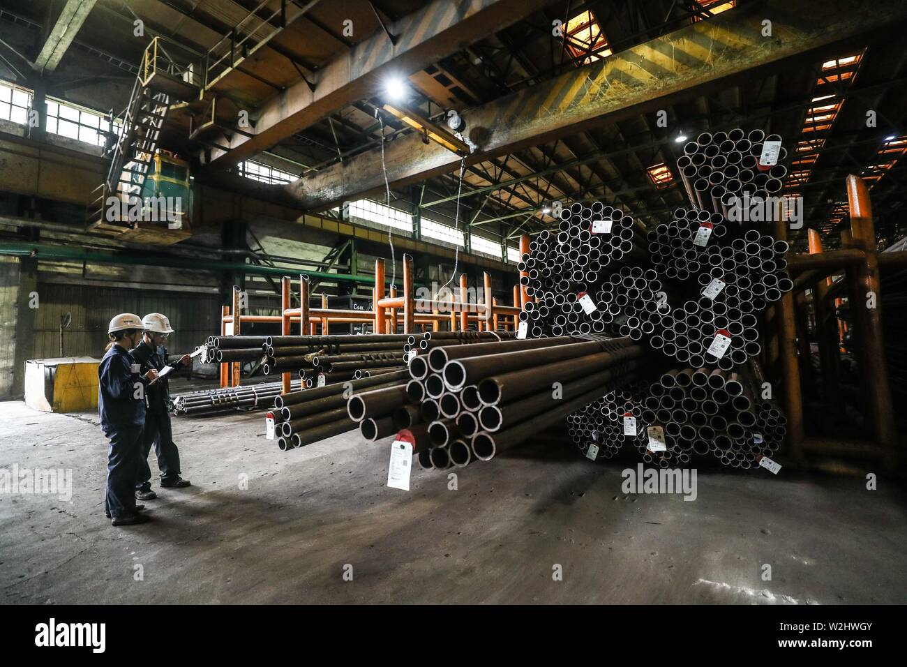 Beijing, China's Liaoning Province. 5th July, 2019. Workers inspect seamless steel tubes at a plant of Ansteel Group Co., Ltd. in Anshan, northeast China's Liaoning Province, July 5, 2019. Credit: Pan Yulong/Xinhua/Alamy Live News - Stock Image