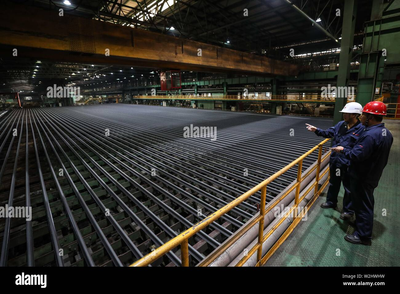 Beijing, China's Liaoning Province. 5th July, 2019. Workers inspect the production of steel rails at a plant of Ansteel Group Co., Ltd. in Anshan, northeast China's Liaoning Province, July 5, 2019. Credit: Pan Yulong/Xinhua/Alamy Live News - Stock Image