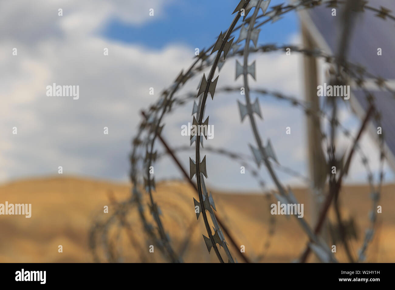 Barbed wire drawn in circles against a background of mountains - Stock Image