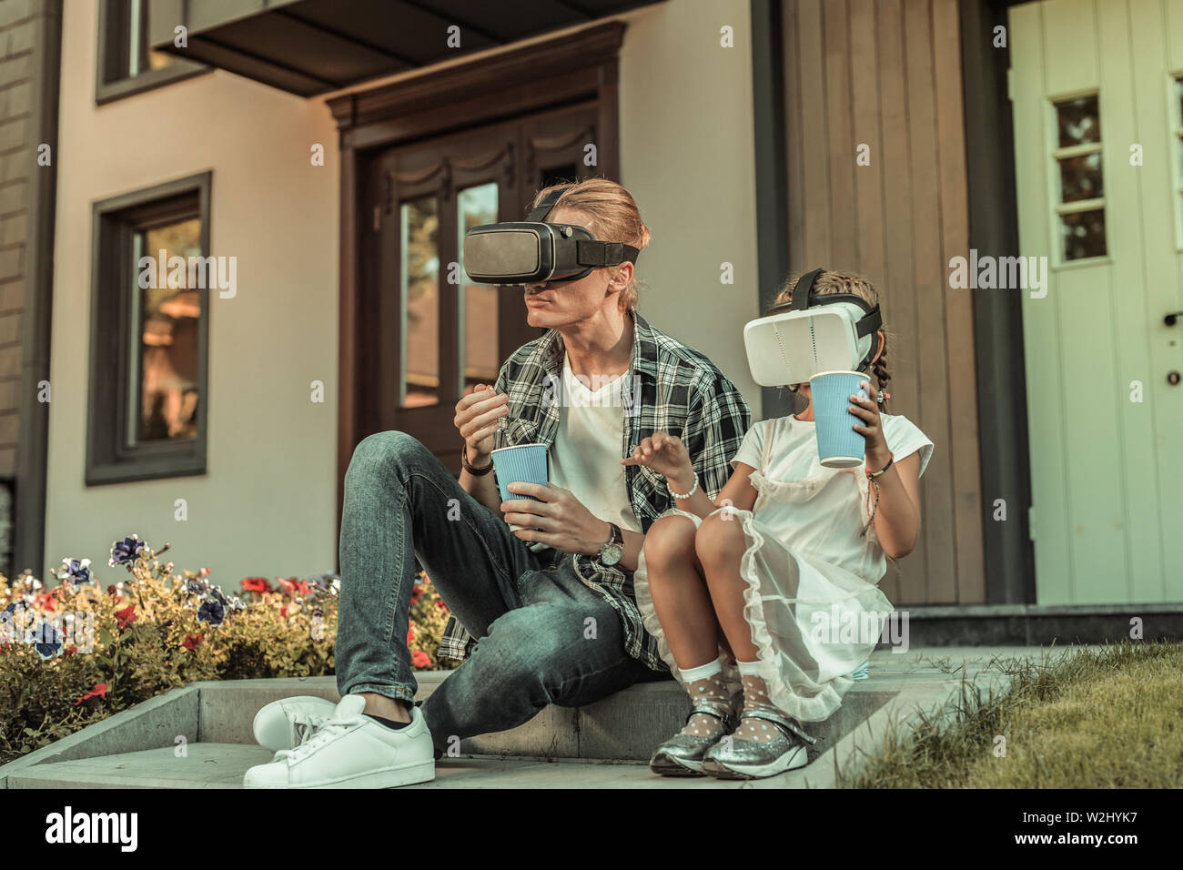 Modern blonde father sitting on the porch with his daughter Stock Photo
