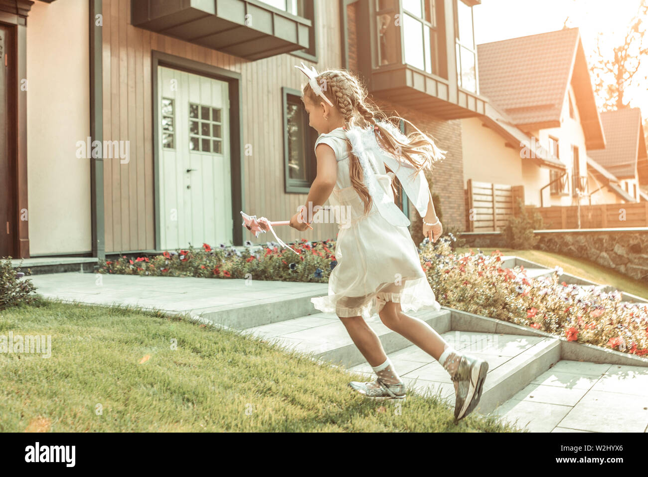 Sportive long-haired girl in white dress running on the porch Stock Photo