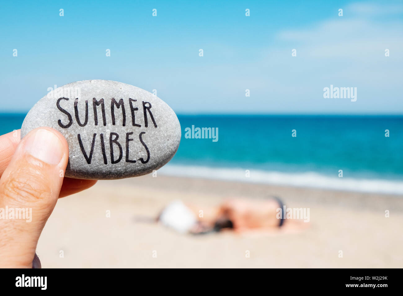 closeup of a caucasian man on the beach holding a stone, with the text summer vibes written in it, and some unrecognizable people relaxing and the sea Stock Photo
