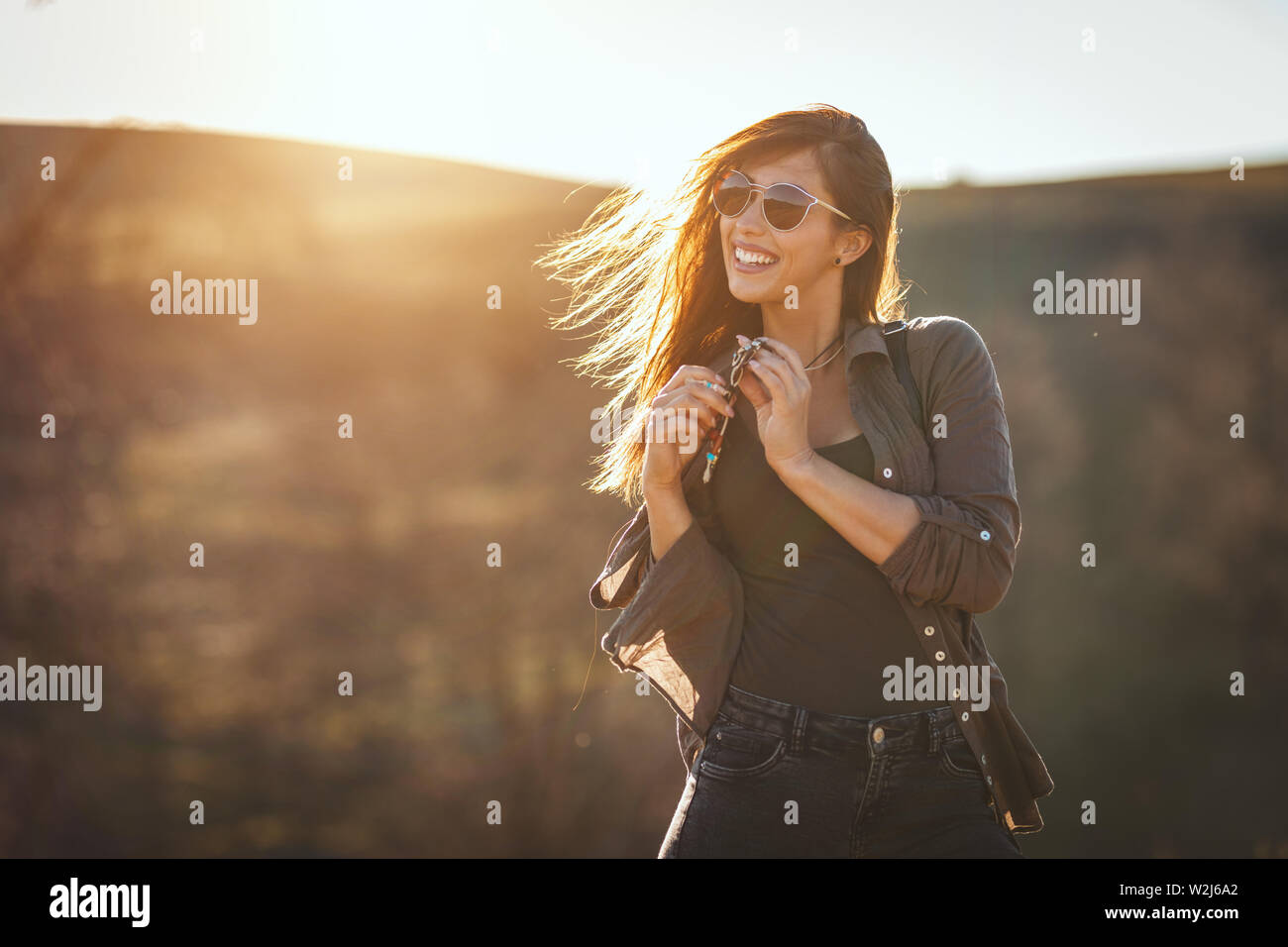 Happy woman is enjoying landscape in mountains looking at the distant hilly landscape outdoor, llooking at the distant hilly landscape outdoor and hav Stock Photo
