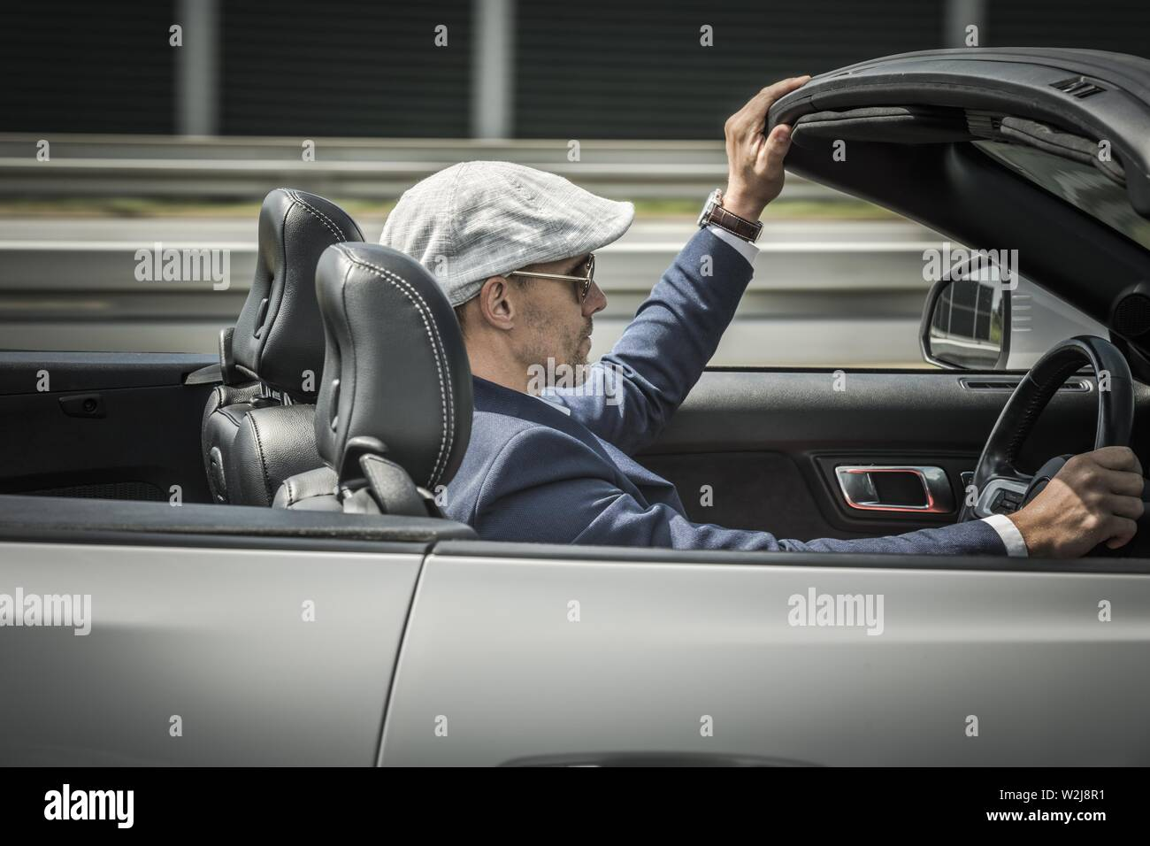 Convertible Car Freedom Drive. Caucasian Driver in His 30s Wearing Stylish Beret Behind the Wheel of Modern Cabriolet Vehicle. - Stock Image