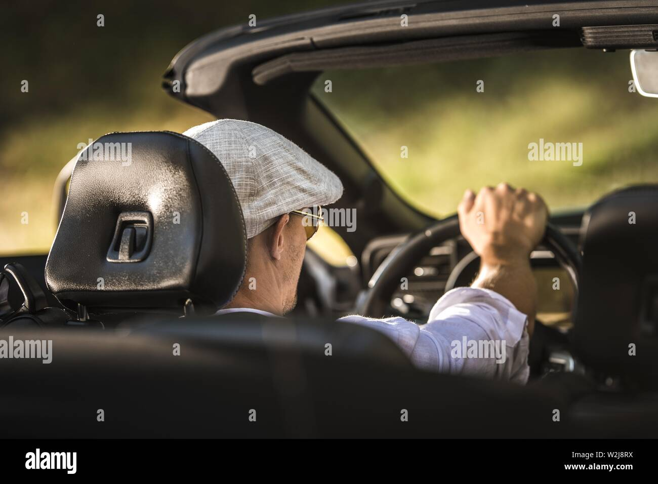 Caucasian Men in His 30s Inside Convertible Vehicle with Open Roof on His Road to Destination. - Stock Image