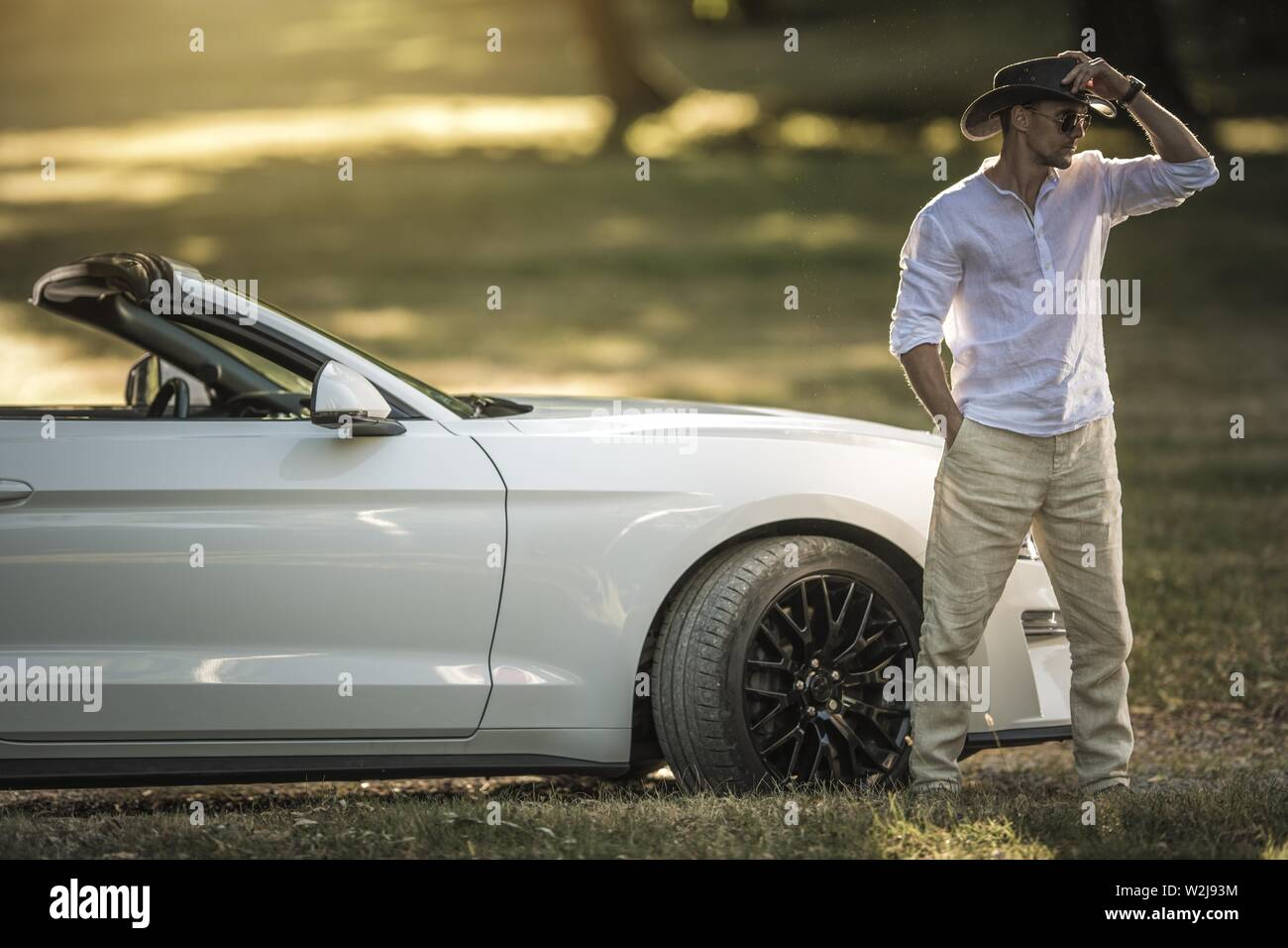 Modern Road Cowboy. Caucasian Men Wearing Western Style Hat in Front of His Modern Convertible Car. Sunny Summer Day in the Far West. Stock Photo