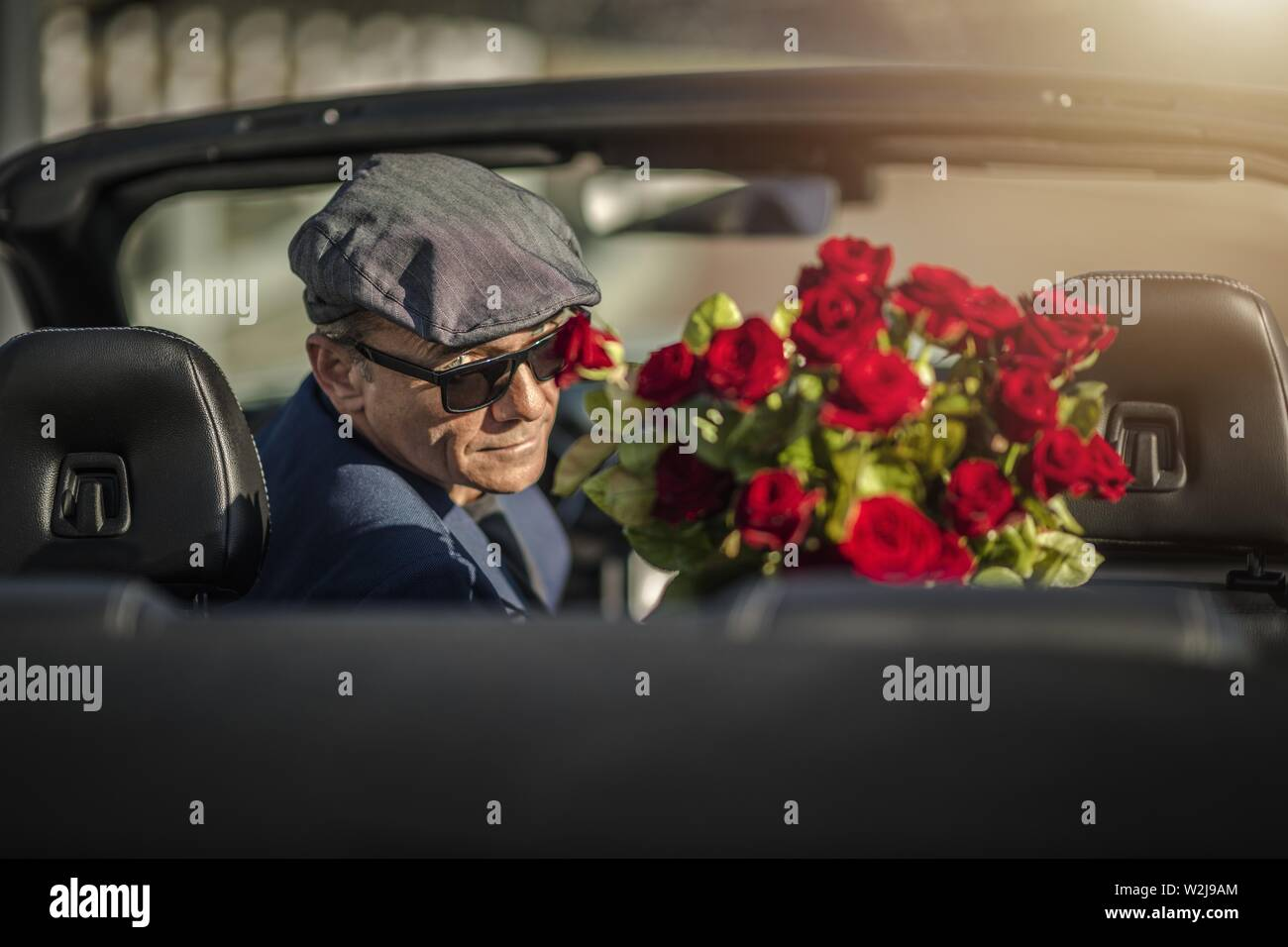 Sugar Daddy Eyes Seduction. Attractive Caucasian Men with Roses Awaiting His Girlfriend While Seating in a Convertible Car. - Stock Image
