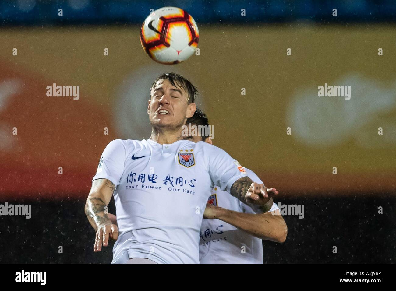 Brazilian football player Roger Krug Guedes, known as Roger Guedes, top, of Shandong Luneng Taishan heads the ball against Beijing Renhe in their 16th round match during the 2019 Chinese Football Association Super League (CSL) in Beijing, China, 7 July 2019. Shandong Luneng Taishan defeated Beijing Renhe 2-0. Stock Photo