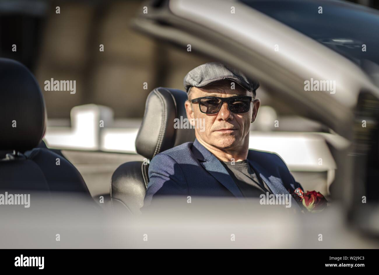 Attractive Retired Caucasian Men in Modern Cabriolet Car. Convertible Road Trip. Retirement Concept. - Stock Image