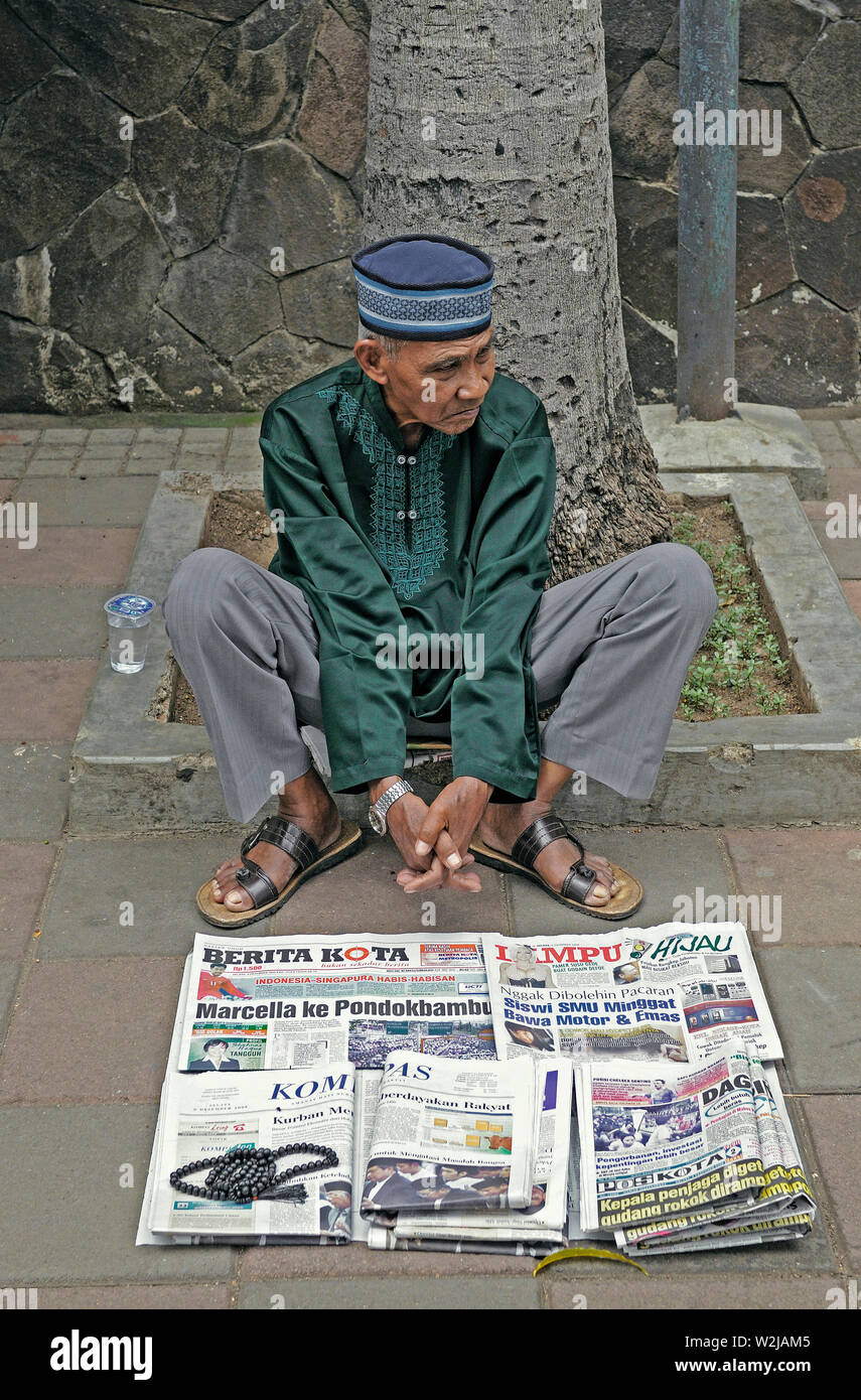 jakarta, dki jakarta/indonesia - december 09, 2008: an old man selling newspapers on jalan m h thamrin in central jakarta - Stock Image