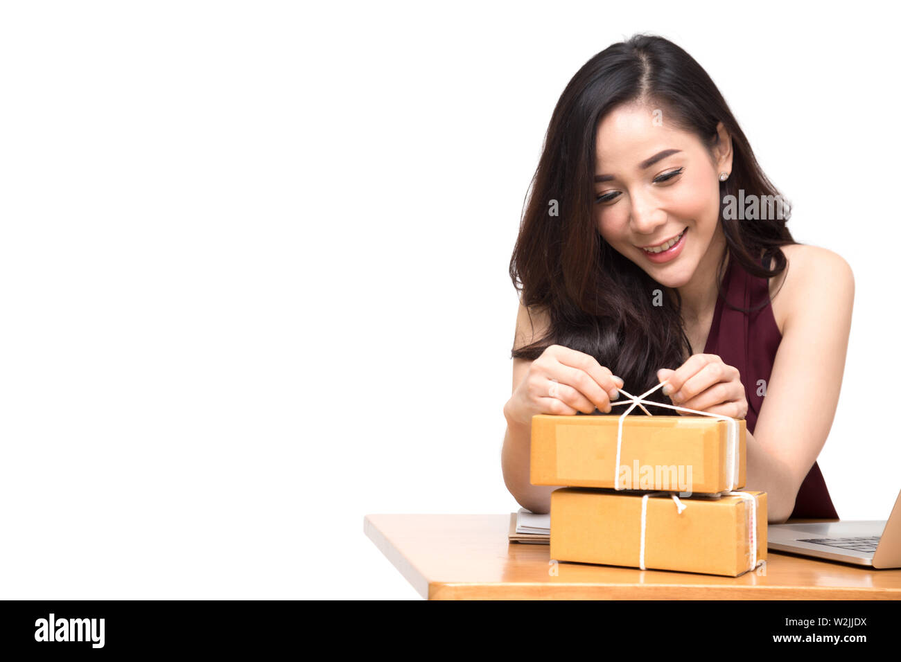 Asian women packing parcel on the table and white background, Female receive cardboard box from buying online orders, Shipping delivery and shopping b - Stock Image