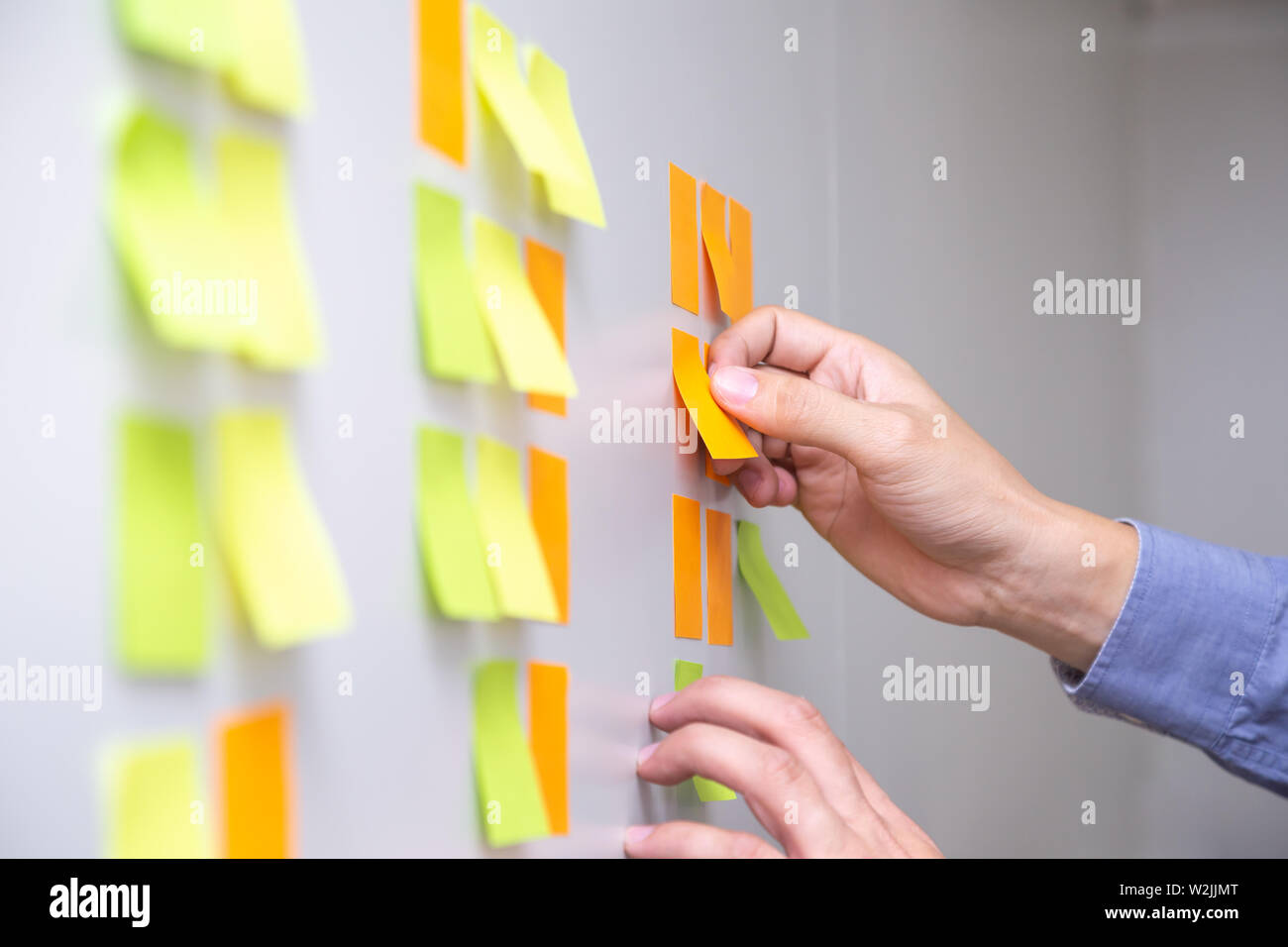 IT worker tracking his tasks on kanban board. Using task control of agile development methodology. Man attaching sticky note to scrum task board in th - Stock Image