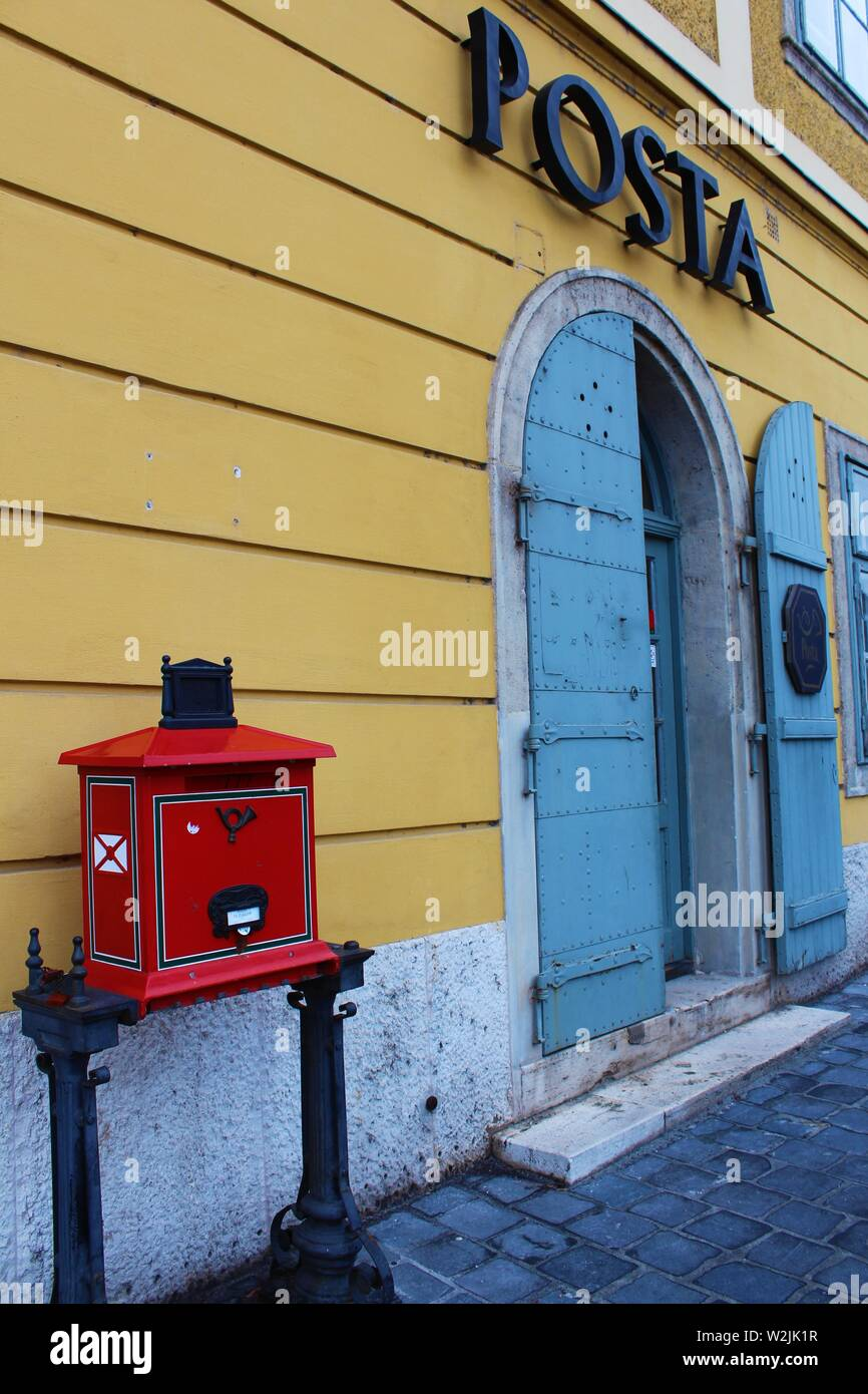 A traditional, red, freestanding postbox, on the street outside the 'Posta' (post office), in the Castle Hill district of Buda, Budapest, Hungary. Stock Photo