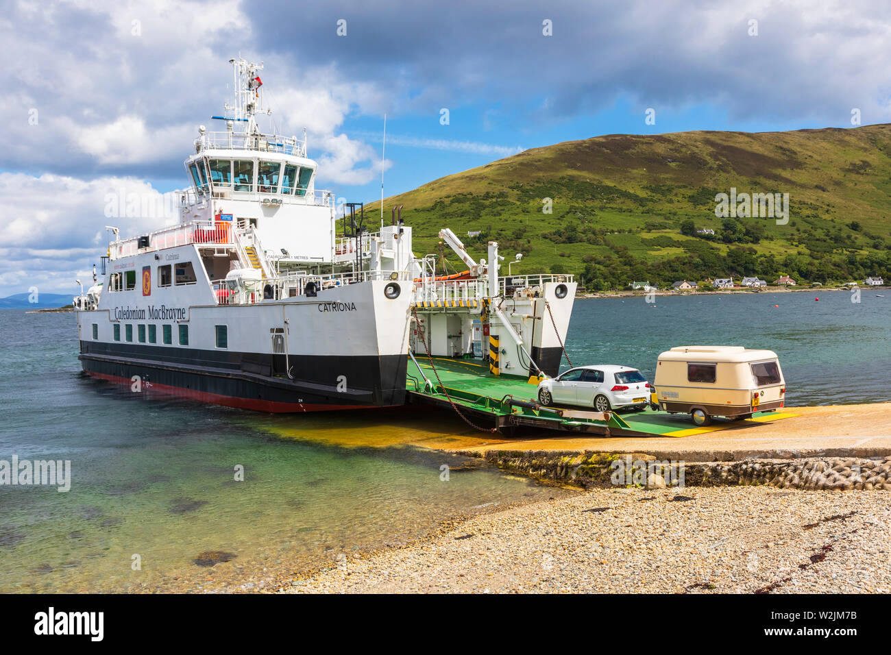 Car and caravan embarking onto the Caledonian MacBrayne car ferry Catriona at the slipway at Lochranza, Isle of Arran on the Firth of Clyde - Stock Image