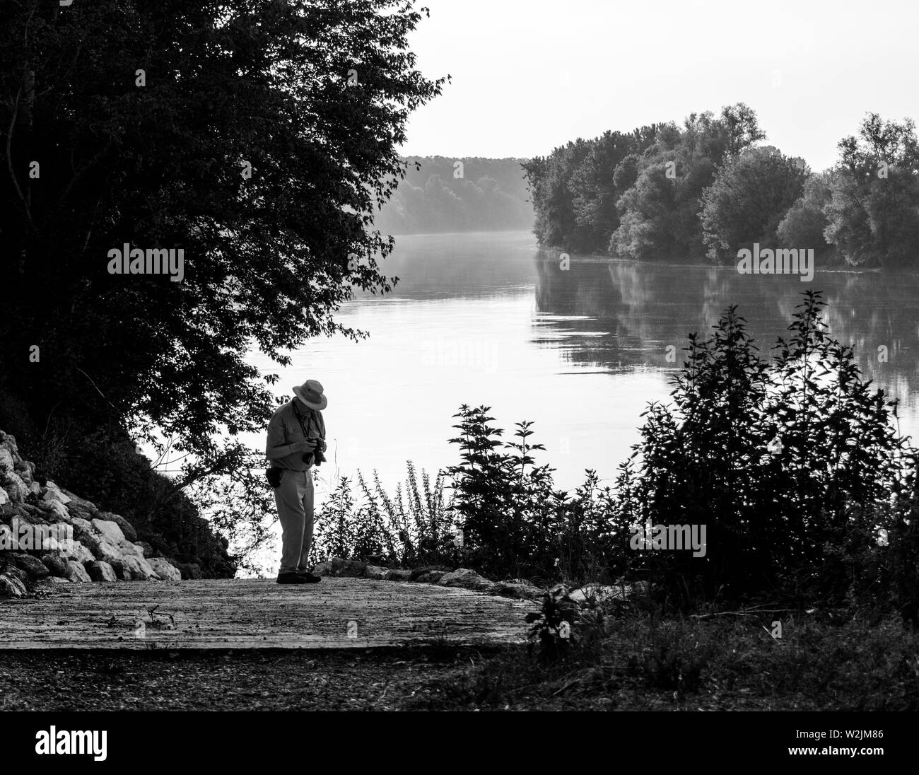 A figure on the riverbank taking photgraphs - Stock Image