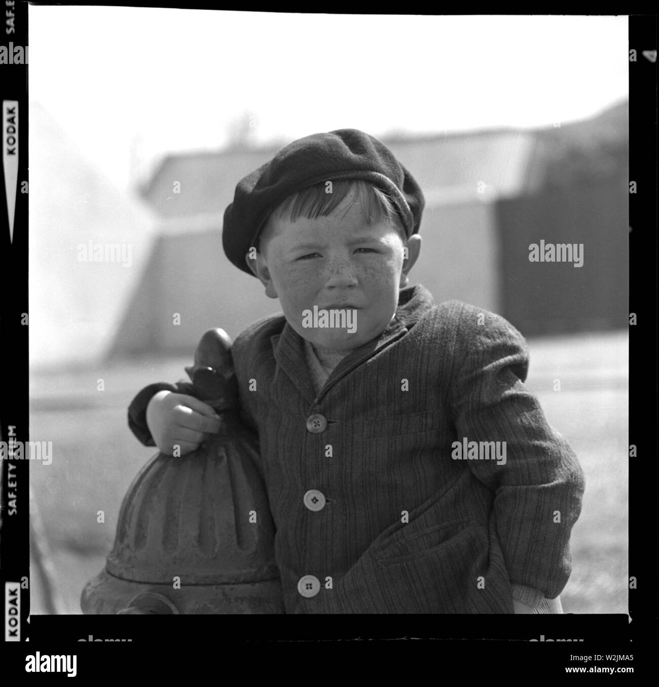 A telling portrait of a young boy, probably near the Sandyford area in Dublin, Ireland c1960. Note the three different buttons on his jacket and jaunty beret. Photo by Tony Henshaw - Stock Image