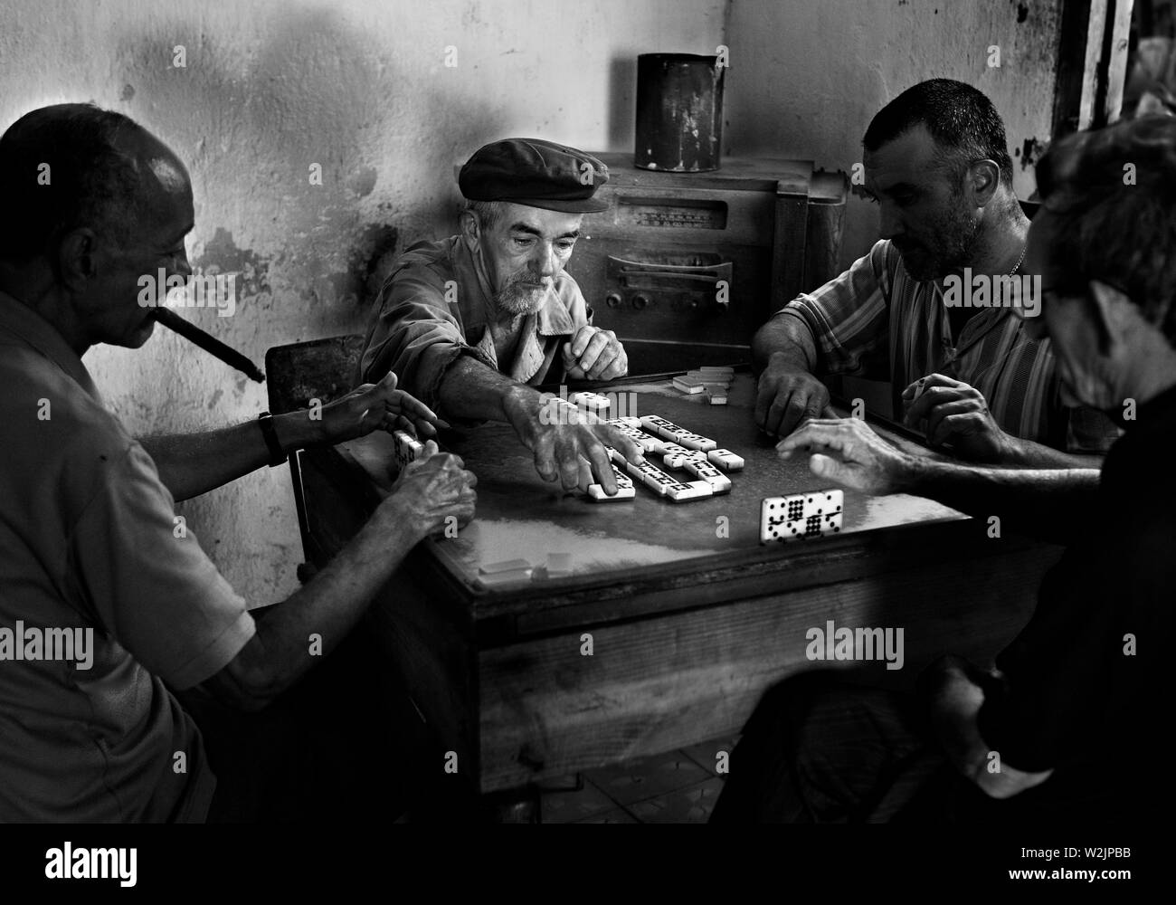 Men playing dominoes in a house in Remedios. - Stock Image