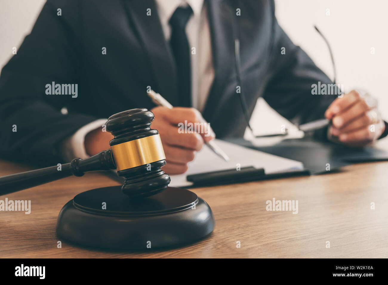 Legal law, advice and justice concept, counselor lawyer or notary working on a documents and report of the important case and wooden gavel, brass scal Stock Photo