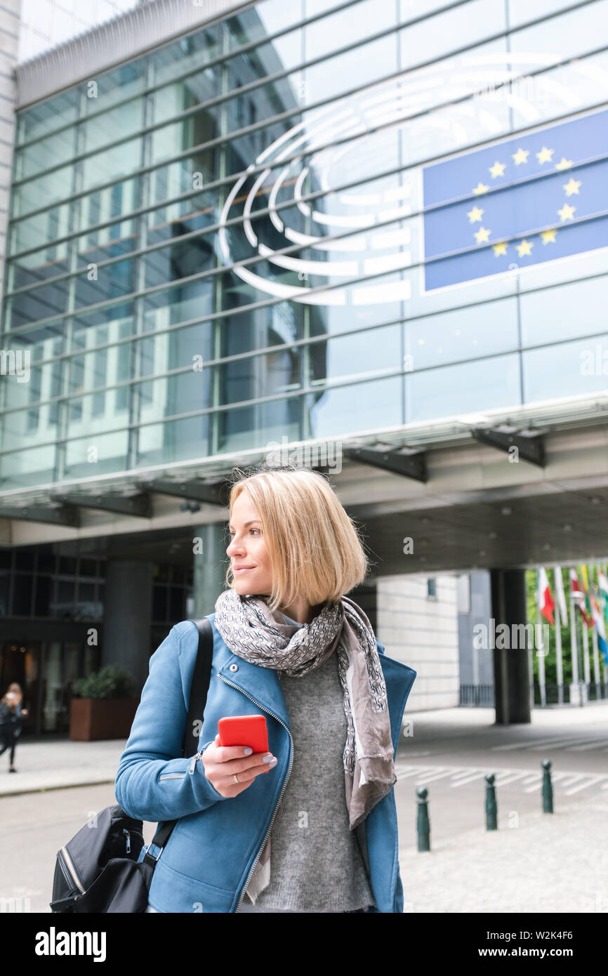 A young woman stands with a telephone in her hands opposite the European Parliament building in Brussels, Belgium. - Stock Image