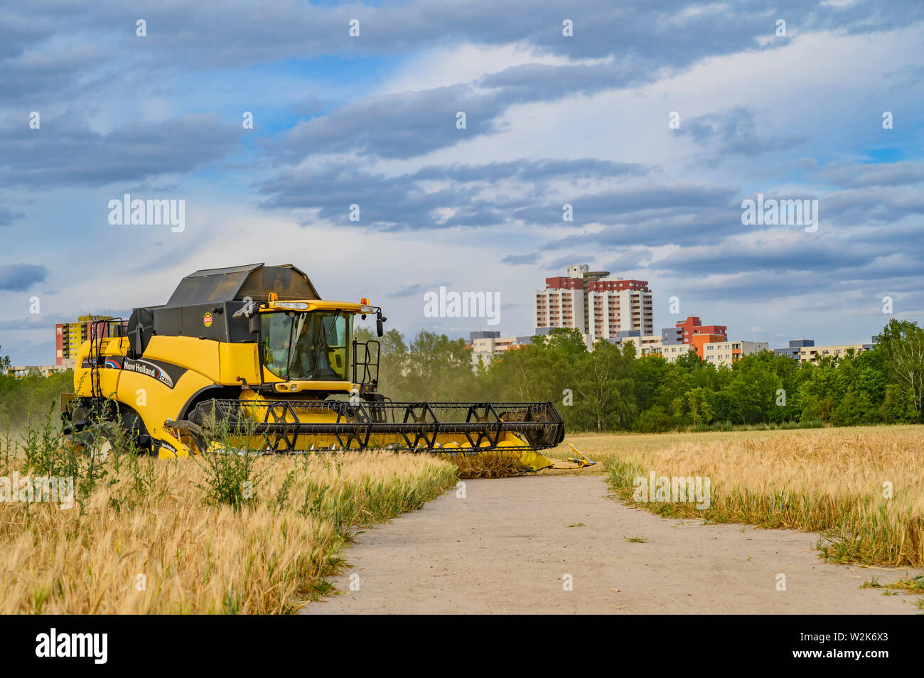 Berlin, Germany - July 05, 2019: Side view of a moving combine harvester on a field near Berlin under a cloudy sky. Stock Photo